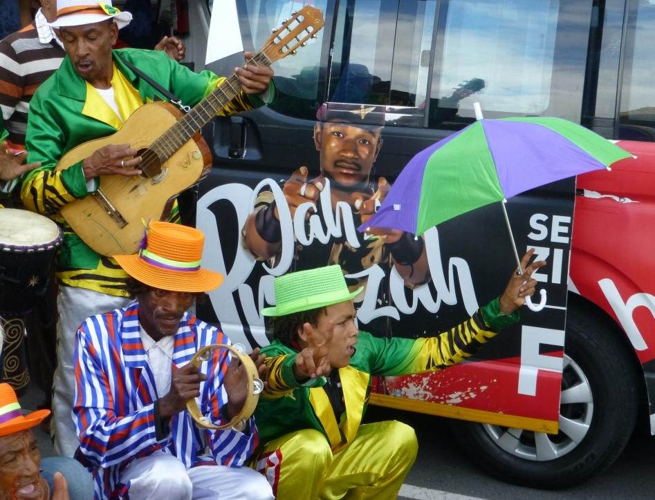 """Afrique Afrique du sud Le Cap Cape Town musique orchestre de rue minstrels couleurs fête Un orchestre de """"minstrels"""" sur le quai du port de Hout Bay près du Cap en Afrique du Sud, devant un """"combi"""" ou bus collectif populaire du pays"""