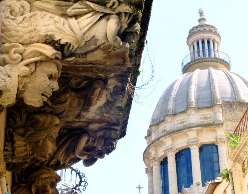 Une foule de personnages sous ce balcon semble regarder le Duomo di San Giorgio au centre de Ragusa Ibla