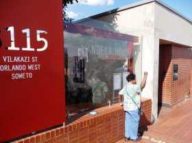 Afrique du Sud Johannesburg Soweto Apatheid prix Nobel de la paix Mandela Tutu Le poing levé devant la maison de Mandela, beaucoup de visiteurs, métis, noirs ou blancs se font photographier