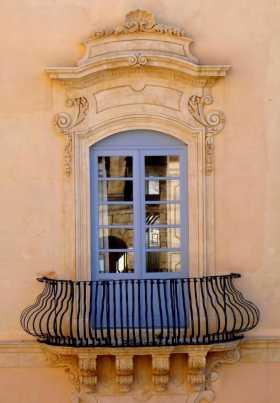 Méditerranée Italie Sicile Noto fenêtres balcons Mur crème, rembarde galbée, fenêtre pompeuse, reflet du monument d'en face dans les vitres