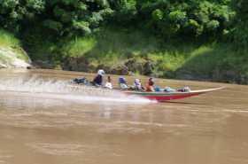 Un speed boat glissant à 70 km/h sur le Mékong avec des passagers casqués
