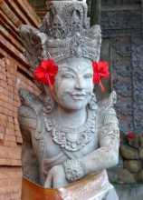 Indonésie Bali île art beauté Statue hindoue parée de fleurs d'hibiscus et d'une ceinture en tissu